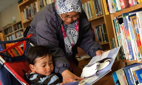 A young muslim mother reading to her son in Lampeter public library, Ceredigion Wales UK
