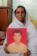 Jan Bibi holds a photo of her 30-year-old son Rehman, who was abducted and killed in Karachi.