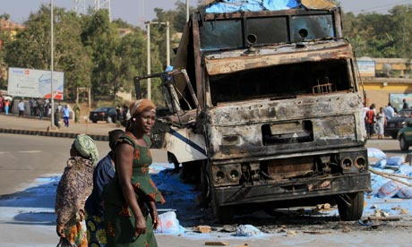 People walk past the wreckage of a truck destroyed in an explosion in the city of Jos.