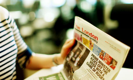 A woman reads The London Weekly freesheet