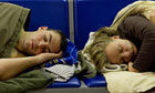 Two people sleep on seats at Gatwick airport