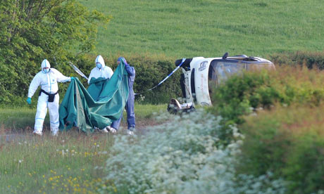 Police forensic officers examine a car containing a body near Seascale, Cumbria