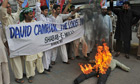 Pakistani activists burn an effigy of David Cameron
