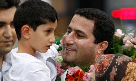 Shahram Amiri carrying his son