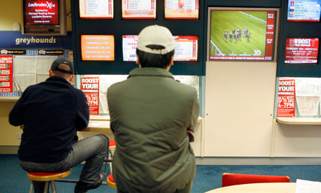Punters watch a horse race in a betting shop