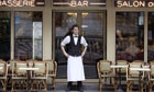 A Paris waiter waits for customers outside his restaurant,