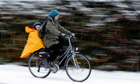 A woman and child cycle during a snow shower in Loughborough