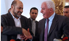 Hamas' Musa Abu Marzuka and Fatah Azzam al-Ahmad shake hands