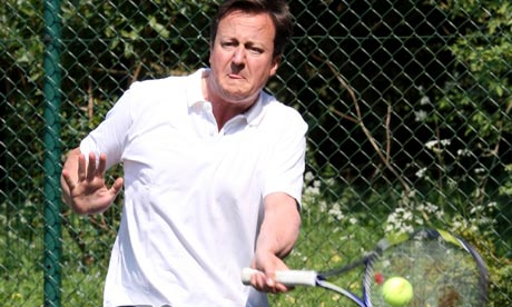 Britain's Prime Minister David Cameron plays a shot during a charity tennis match
