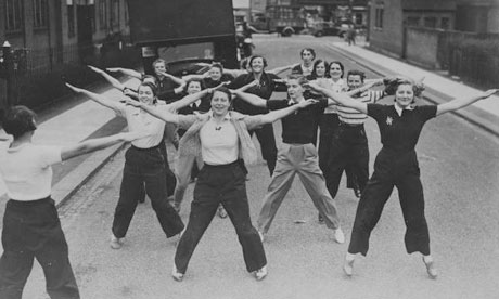 Volunteer female ambulance drivers take part in an aerobics class in a London street, 1939.