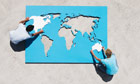 Aerial view of man and woman outdoors with world map puzzle. Image shot 2007. Exact date unknown.