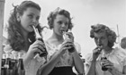 Three teenage girls drinking bottles of soda with straws circa 1956