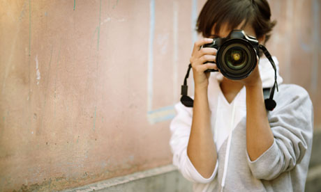 female photographer with professional SLR camera,