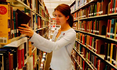 A young woman picking a book from a library