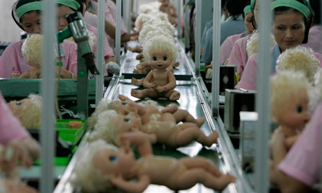 Labourers work at the production line at a toy factory in Panyu