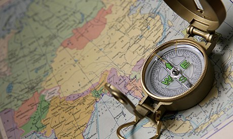 A compass on the world map of the atlas