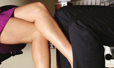 A woman rubbing her foot against a man's leg
