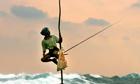 TRADITIONAL SRI LANKAN FISHERMEN FISH FROM ATOP POLES NEAR GALLE.