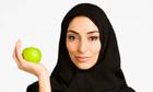 Middle Eastern woman in burkha holding apple