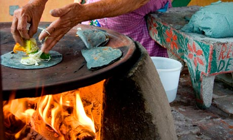 A woman cooking blue corn tortillas and cheese in Mexico