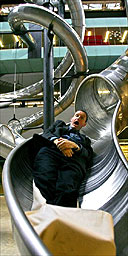 A visitor has a ride on Carsten Holler's Test Site at Tate Modern