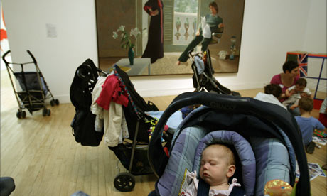 A baby in a pushchair in front of David Hockney's Mr and Mrs Clark and Percy at Tate Britain