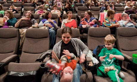 Mothers and babies wait for a movie to begin