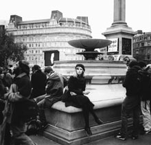 A young woman relaxes on the edge of the fountain in Trafalgar Square