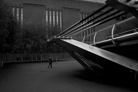 A man walks between the Millenium Bridge and the tate Modern Art Gallery in London
