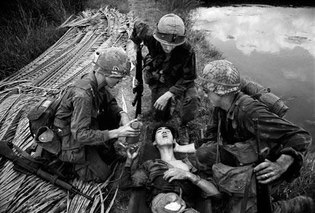 Mostrando compasión American GI hacia un soldado del Vietcong lesionado