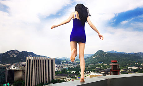 Self-portrait of South Korean artist Ahn Jun, running along a tall building in Seoul