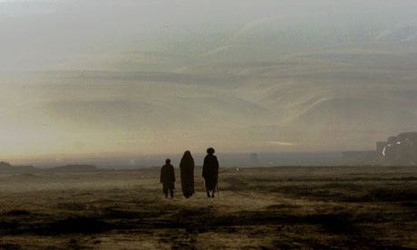 AFGHAN FAMILY WALK THROUGH DESERT NEAR KHOJA BAHAWUDDIN.