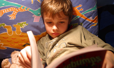 Young boy reading a book. A boy reading a book at bedtime.