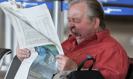A newspaper reader yawns