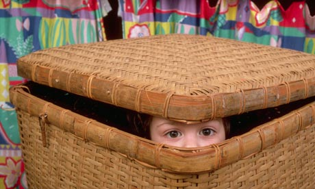 A boy hides in a basket