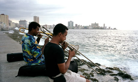 Two musicians play trombones on the sea wall in Havana, Cuba