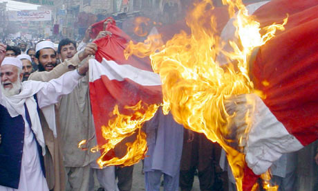 Protesters in Peshawar burn a Dutch flag in protest at the Muhammad cartoons