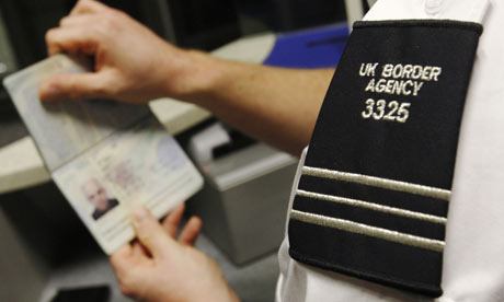 UK Border agent checks a passport