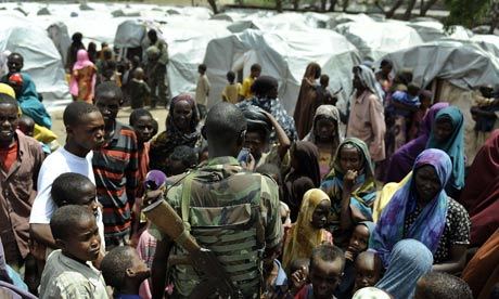 Somalis gather around a soldier of the Africa Union peacekeeping mission in Somalia at a camp