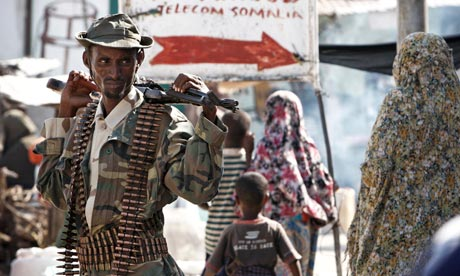A Somali government soldier stands guard at a market in Mogadishu