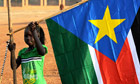 A girl holds a South Sudan flag
