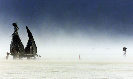 A cyclist rides through a sand storm at the Burning Man festival