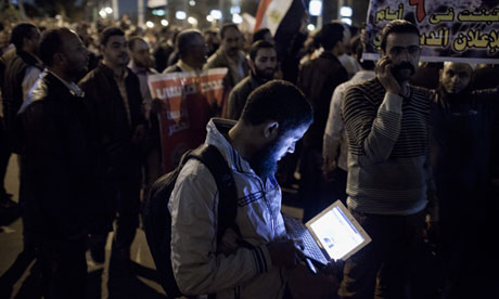 A Morsi supporter checks his laptop during protests outside the Presidential Palace in Cairo, Egypt
