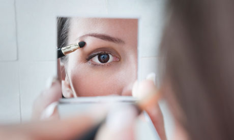 Young woman applying eye makeup in a vanity mirror