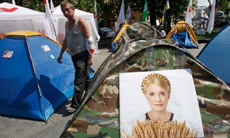 A man walks past tents for supporters of the jailed opposition leader Yulia Tymoshenko