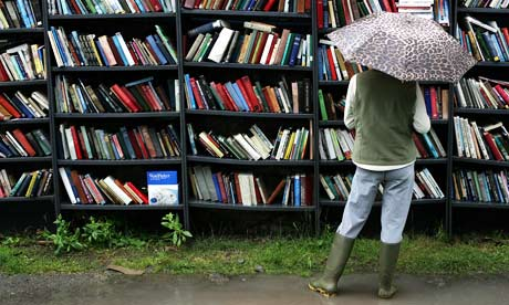 A woman wearing wellington boots and holding an umbrella, looks at outdoor book shelves in the rain