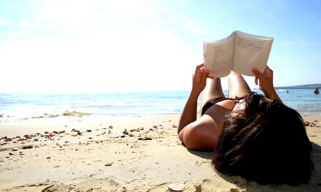A woman reading a book on a beach in summer