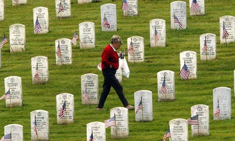 woman walking among headstones in national cemetery in California