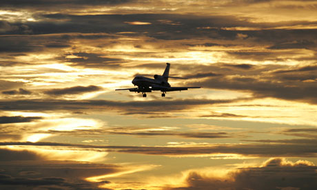 a plane comes in to land against a sunset sky