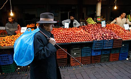 A man walks past fruit stalls at Athens main food market
